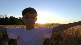 小男孩连续十字架在日落的麦田 慢的行动