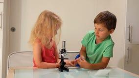 小男孩递一张显微镜幻灯片给女孩 影视素材
