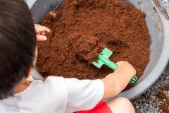 小男孩铲起对混杂的土壤,准备种植树 图库摄影
