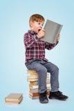 小男孩阅读书,当坐堆书时 免版税库存照片