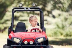 小男孩驱动一辆微型电车在公园 免版税库存图片