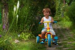 小男孩骑马三轮车 免版税库存图片