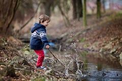 小男孩,做大飞溅在池塘 库存照片