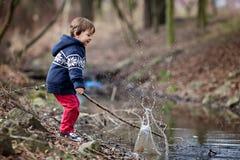 小男孩,做大飞溅在池塘 免版税库存照片