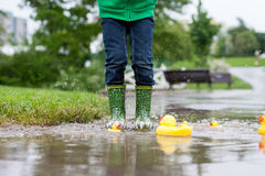 小男孩,跳跃在泥泞的水坑在公园,橡胶鸭子我 免版税图库摄影