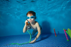 小男孩水中游泳并且充当与手机的水池 图库摄影