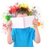 小男孩读书与油漆的艺术书在白色 库存图片
