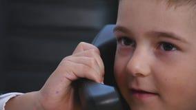 小男孩说在电话里在办公室 关闭 免版税库存图片