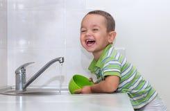 小男孩洗涤的盘 免版税库存照片