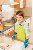 小男孩洗涤盘画象在厨房里 图库摄影