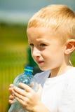 小男孩从瓶的饮料水,室外 免版税图库摄影