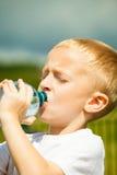 小男孩从瓶的饮料水,室外 免版税库存图片