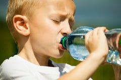 小男孩从瓶的饮料水,室外 免版税库存照片