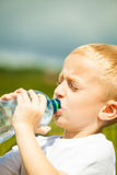 小男孩从瓶的饮料水,室外 库存图片