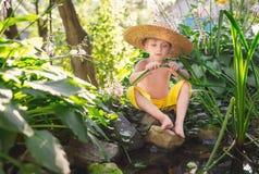 小男孩画象草帽和黄色裤子的在池塘的岸绿草的 图库摄影