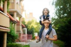 小男小学生坐父亲肩膀和紧贴到他的头 免版税库存照片