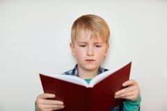 小男小学生室内射击有公平的头发的在他的手上的拿着一本书 读书的一个小男孩被隔绝在白色backg 库存照片
