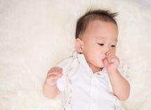 小男婴吮他的在嘴的7个月拇指手指 库存图片