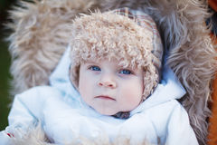小男婴在温暖的冬天给室外穿衣 库存照片