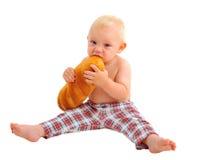 小男婴用大面包,隔绝在白色背景 免版税库存照片