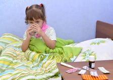 小病的女孩在床上坐并且喝从玻璃的水 库存照片