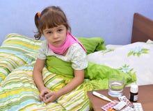 小病的女孩在床上坐 免版税图库摄影