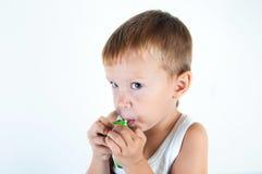 小病的男孩为呼吸使用了医疗浪花 使用他的哮喘泵浦的小男孩 为过敏使用一朵浪花 逗人喜爱的婴孩享受s 免版税库存照片