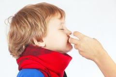小病的男孩在鼻子使用了鼻孔喷射 免版税库存照片