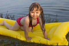 小白女孩孩子在lak的可膨胀的床垫摆姿势 免版税库存照片