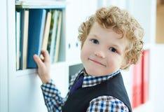小白种人卷曲男孩在图书馆里选择一本书 免版税库存图片