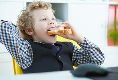 小白种人男孩在工作场所嚼了一个三明治在办公室 库存照片