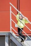 小白种人男孩画象帽子的保持楼梯路轨对红色金属墙壁在城市围场 免版税库存照片