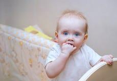 小白肤金发的女孩与站立在床画象的蓝眼睛和一张圆的面孔的1岁 孩子咬住他的手 白色家庭inte 库存照片