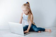 小白肤金发的女孩与银色颜色膝上型计算机坐在家被隔绝的白色木地板 复制空间 免版税库存图片