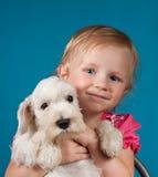 小白肤金发的女孩和她的小狗 免版税库存照片