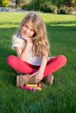小白肤金发的女孩在庭院里 免版税库存照片