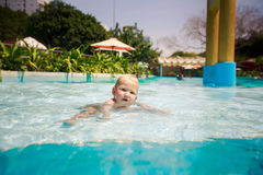小白肤金发的女孩在旅馆游泳池沐浴微笑戏剧 库存图片