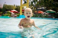小白肤金发的女孩在水池中透明水站立啼声  库存图片