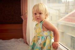 小白肤金发的女孩坚持窗口边看法 免版税库存图片