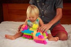 小白肤金发的女孩演奏与父亲的玩具建设者沙发的 免版税图库摄影