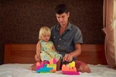 小白肤金发的女孩演奏与父亲的玩具建设者沙发的 库存图片