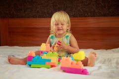 小白肤金发的女孩演奏玩具建设者坐沙发 免版税库存照片