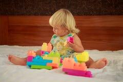 小白肤金发的女孩演奏玩具建设者 库存图片