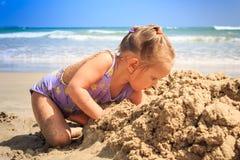 小白肤金发的女孩蹲修造在海滩特写镜头的沙子城堡 库存照片