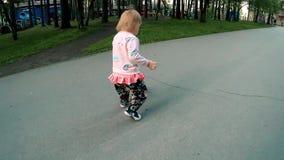 小白肤金发的女孩追捕在公园晴天迅速慢动作的球 股票视频