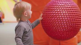 小白肤金发的小孩微笑并且推挤做它的大fitball摇摆 影视素材
