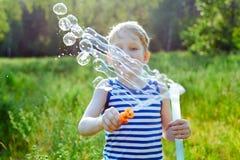 小白肤金发的男孩在公园做泡影肥皂外面 库存图片