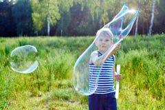 小白肤金发的男孩在公园做泡影肥皂外面 免版税库存图片