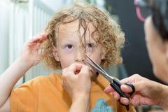 小白肤金发的男孩得到他的头发切开 免版税库存图片