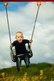 小白肤金发的男孩获得乐趣在操场 使用在摇摆的儿童孩子室外 库存图片
